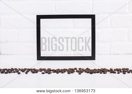 Front view of bright table with coffee beans and blank see-through picture frame on white brick wall background. Mock up