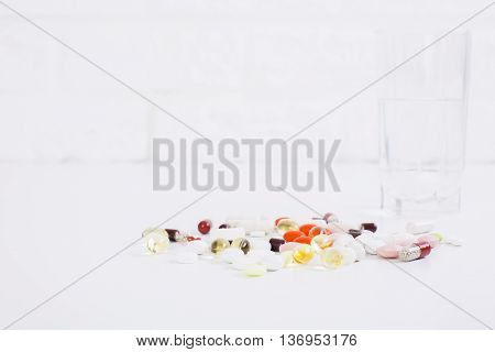 Closeup of white surface with different pills capsules and glass of water on brick wall background