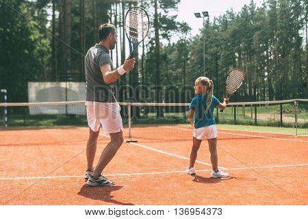 Training together. Full length rear view of father in sports clothing teaching his daughter to play tennis while both standing on tennis court
