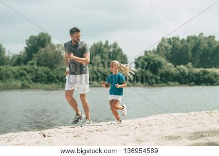 Living a healthy life. Full length of cheerful father and daughter in sports clothes jogging at the riverbank together