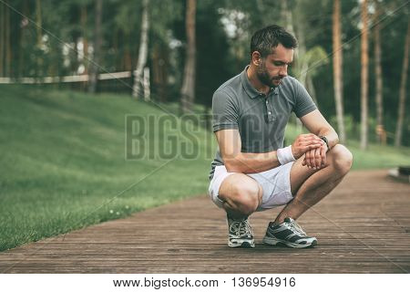 New result! Confident mature man in sports clothing looking at his wristwatch while crouching in park