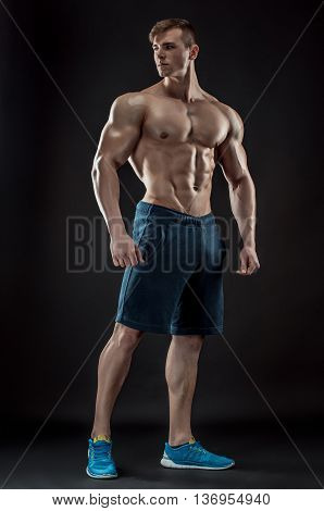 Muscular bodybuilder guy doing posing over black background. Naked torso in jeans.