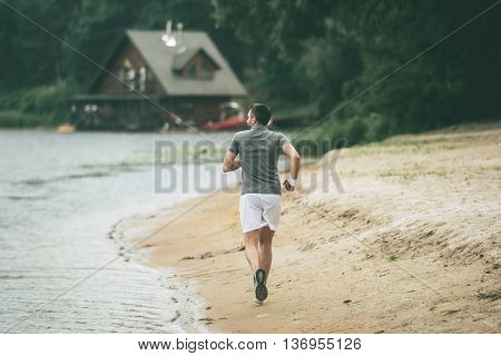 Morning jog. Full length rear view of confident man in sports clothing running along the riverbank