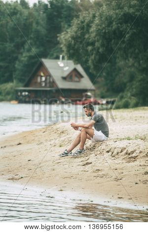 Inspiring with music and fresh air. Handsome young man in sports clothing wearing headphones and looking away while sitting on the riverbank