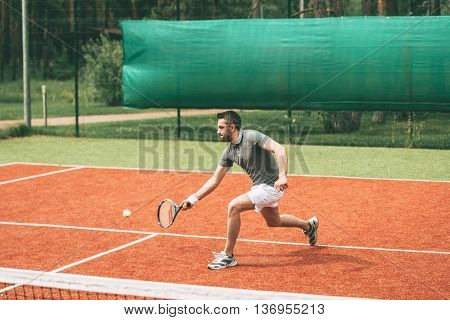 Man playing tennis. Confident young man in sports clothes playing tennis on tennis court