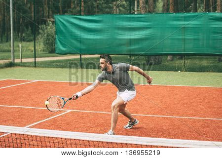 Playing tennis. Confident young man in sports clothes playing tennis on tennis court
