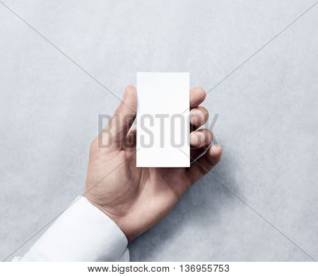 Hand holding blank vertical white business card design mockup. Clear calling card mock up template hold arm. Visiting pasteboard paper surface display front. Small pure offset card holder presentation