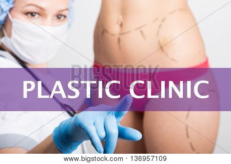 plastic clinic written on a virtual screen. Internet technologies in medicine concept. medical doctor presses a finger on a virtual screen. cosmetic surgery, lifting and breast augmentation.