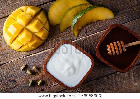 Overhead of mango yogurt and honey for milkshake.