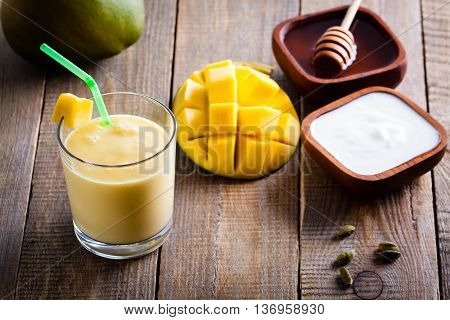 Glass of mango lassi Indian drink made from yogurt with blended mango and honey flavored with cardamom.