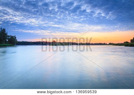 Lake landscape with beautiful sky at sunrise photographed on long exposure.
