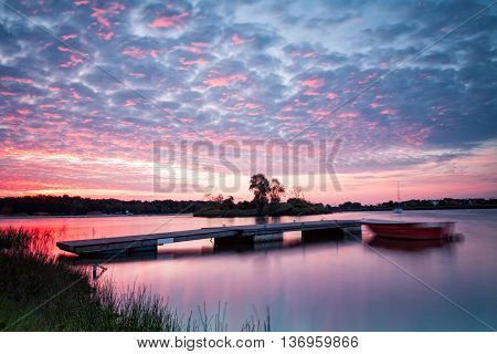Lake landscape with beautiful sky and pier at sunrise photographed on long exposure.