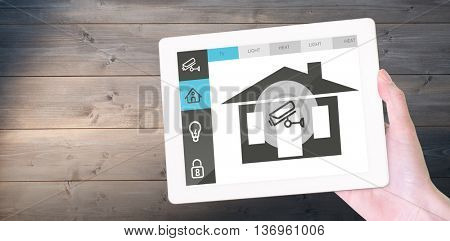 Feminine hand holding tablet against bleached wooden planks background