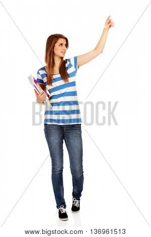 Teenage happy woman holding textbooks and pointing for something