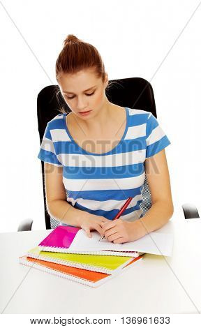 Teenage woman doing homework behind the desk