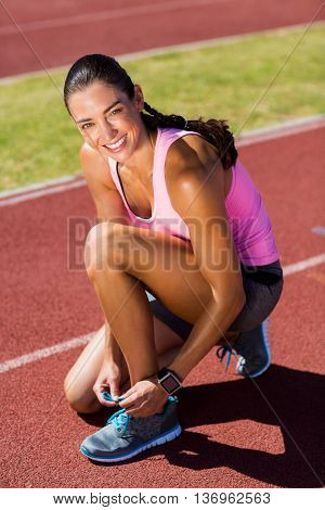 Portrait of happy female athlete tying her running shoes on running track