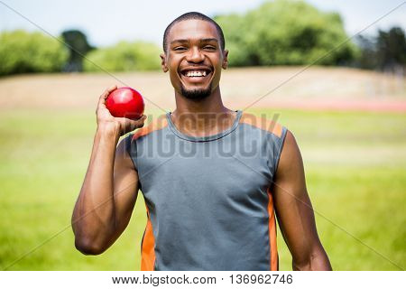 Happy male athlete holding short put ball in a stadium