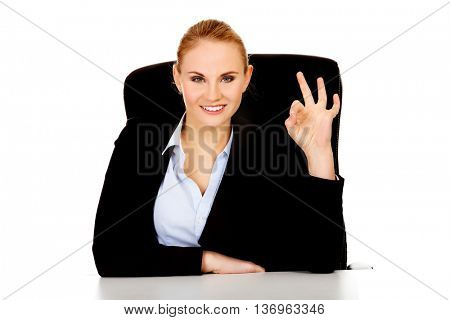 Happy business woman sitting behind the desk and shows OK sign