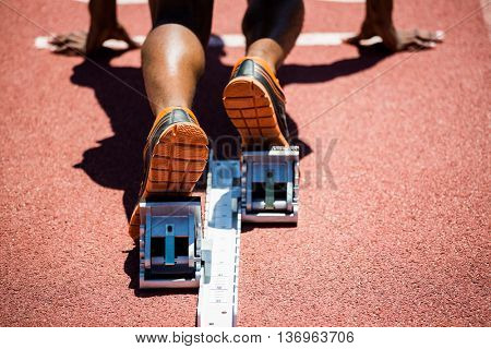 Close-up of feet of an athlete on a starting block about to run