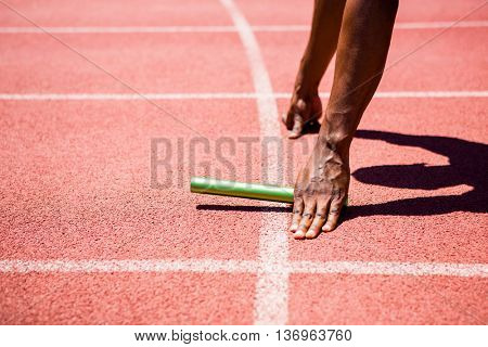 Hands of athlete holding baton on running track
