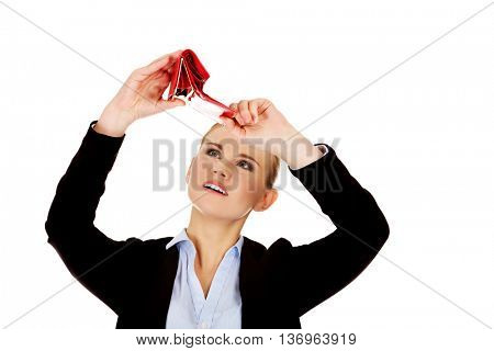 Unhappy business woman looking into her empty wallet