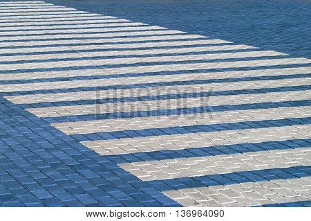 Pedestrian crossing traffic sign.Zebra crosswalk on blue tiles road.