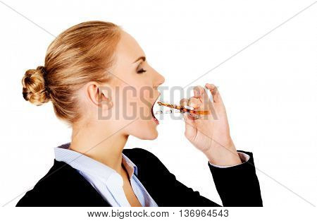 Young business woman trying to eat blister of pills