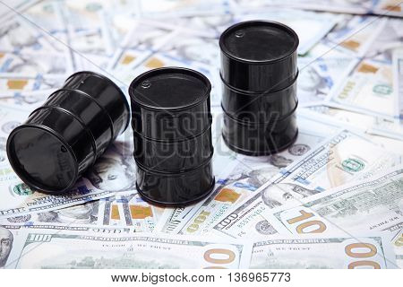 Close-up photo of oil drums on US dollars background