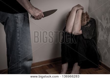 Aggressive man threatening frightened woman with the knife. Selective focus.