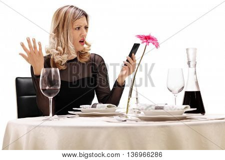 Displeased woman sitting at a restaurant table and reading a message on her phone isolated on white background