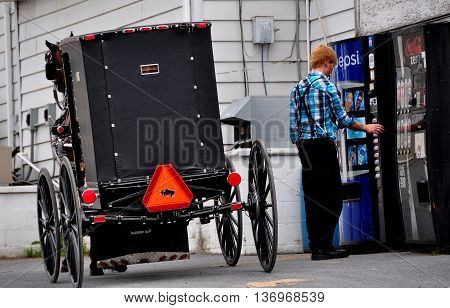 Lancaster County Pennsylvania - June 7 2015: Amish youth next to his parked horse and buggy stops to buy a Pepsi Cola from a vending machine