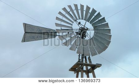Vintage western-ranch style windmill against gray sky.