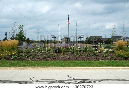 SHOREWOOD, ILLINOIS / UNITED STATES - AUGUST 30, 2015: Flags fly at the Village of Shorewood Towne Center Veterans' Memorial, which honors those who served in the armed forces of the United States.