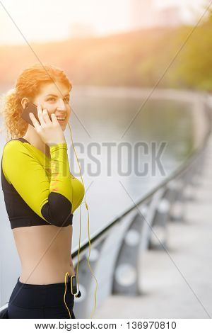 Happy sporty girl talking on phone in park. Image with lensflare