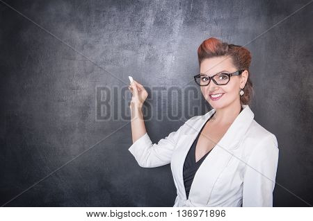 Beautiful Teacher With Piece Of Chalk On Blackboard Background