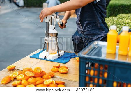 Man squeezes orange juice. Outdoors. orange peel on the table
