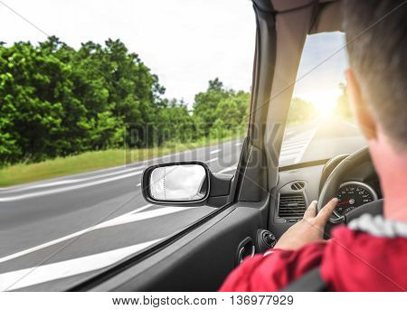 Male driver drives a convertible car on the country road. The view from the cabin, rear view, inside.