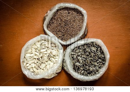 Seeds sunflower pumpkin and linseed. Healthy food in glass in folic bags.