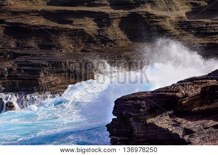 Ocean Waves Crashing against rocks and cliffs with white foam Close-up. Rustic weathered lava rock cliff face