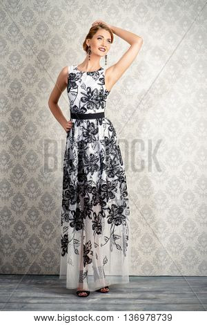 Full length portrait of a charming woman in beautiful evening dress standing by a vintage wallpaper. Jewellery. Fashion shot. Hairstyle.