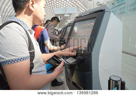 SHENZHEN, CHINA - CIRCA MAY, 2016: man use self check-in kiosk in Shenzhen Bao'an International Airport. It is located near Huangtian and Fuyong villages in Bao'an District, Shenzhen, Guangdong, China