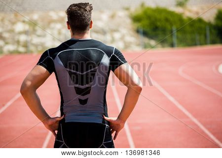Rear view of athlete standing with hands on hip on running track