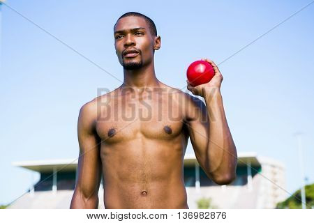 Determined male athlete holding short put ball in a stadium