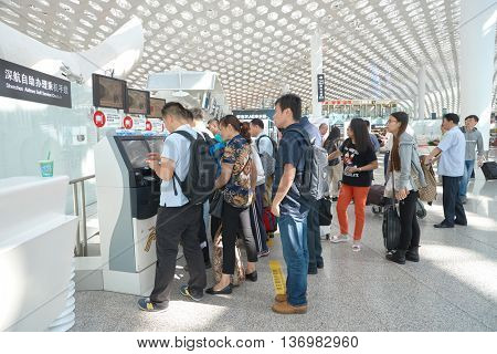 SHENZHEN, CHINA - CIRCA MAY, 2016: people use self check-in kiosks in Shenzhen Bao'an International Airport, located near Huangtian and Fuyong villages in Bao'an District, Shenzhen, Guangdong, China.
