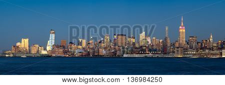 Panoramic view at dusk of Manhattan Midtown West and illuminated skyscrapers with the Hudson River. New York City