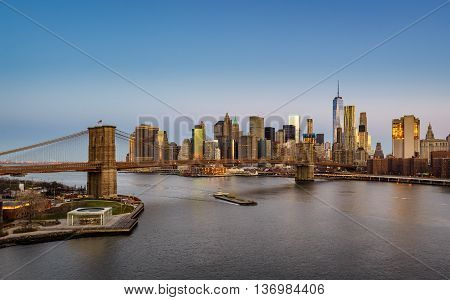 Aerial view of the Brooklyn Bridge at sunrise and Manhattan Lower East Side Financial District skyscrapers. New York City