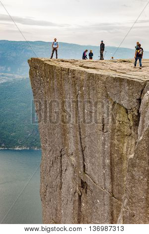 FORSAND, NORWAY - JULY 12, 2015: Group of tourists looking over the edge of Pulpit Rock on Lysefjorden, Norway. Lysefjorden is one of the most famous fjords in Norway.