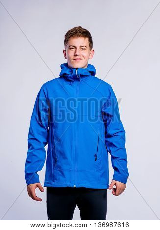 Teenage boy in blue sports jacket, young man, studio shot on gray background