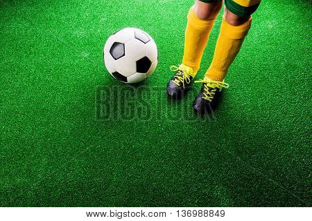 Legs of unrecognizable little football player with soccer ball against artificial grass. Studio shot on green grass.