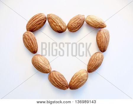 Almonds in heart shape on white background
